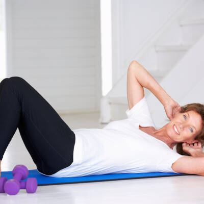 Senior woman doing curl-ups on exercise mat at home